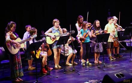 2015 songwriting students, boys and girls, with guitars and fiddles, perform at the culminating concert of the PineCone Bluegrass Camps for Youth on stage at the Cary Arts Center