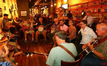 Men and women sit and stand together in a circle on the main level of the Busy Bee Cafe - instruments around the circle include stand-up bass, guitar, banjo, mandolin, dobro (resonator guitar), fiddle, and of course, vocals. Also visible are the Busy Bee's bar, photos hanging on the brick wall opposite the bar, and tables where other folks can enjoy their meal while listening to the jam. Hanging lights illuminate the room.