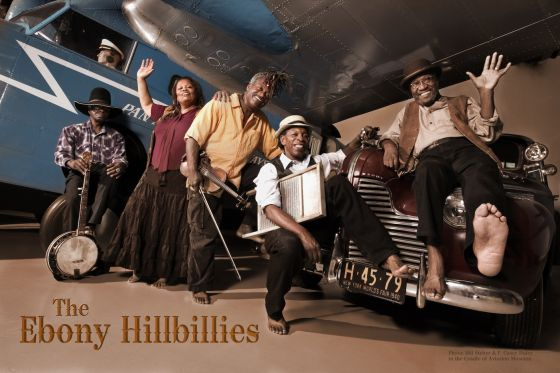 Five members of The Ebony Hillbillies (four men and one woman), some standing, some seated, with an old plane and an old fashioned car in the background. Three of the men have instruments: 1 a banjo, 1 a fiddle, and 1 a washboard.