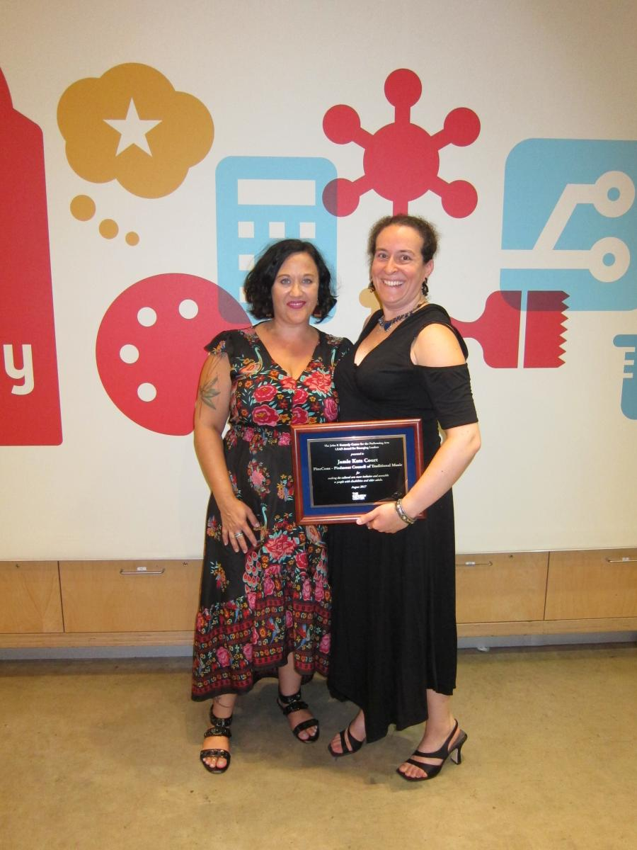 Courtney Wheeler and Jamie Katz Court stand side by side in front of a decorated wall at The Thinkery with the LEAD award plaque.