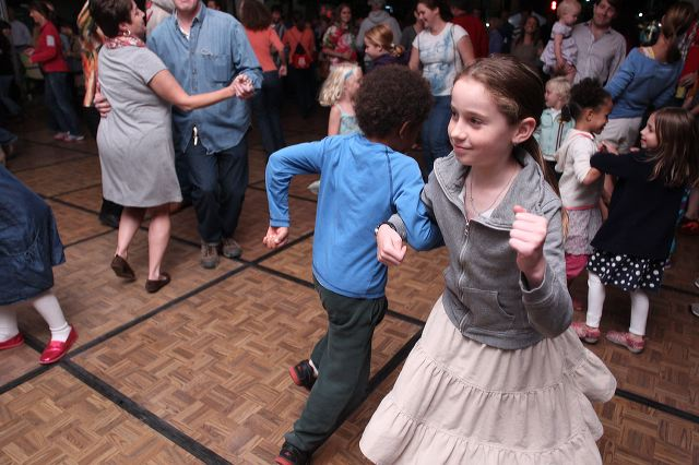 Kids and people of all ages square dancing in the dance tent at the 2013 Wide Open Bluegrass StreetFest; in the foreground, a girl and boy doe-si-doe - the girl's face is visible, her right arm hooked through a boy's right arm; his back is to the camera. In the background, kids and adults  of varying ages dance, smile, and appear to enjoy the music and festivities.