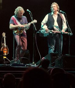 Sam Bush (left) playing mandolin, and Jerry Douglas (right) playing dobro on stage together - each musician has a microphone on a stand in front of him; there's an extra mandolin on a stand to Bush's right. Audience member silhouettes are visible in the foreground.