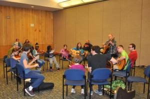 A diverse group of female and male students sit in a circle in a room at Marbles Kids Museum playing fiddles and guitars; facilitator Jef Walter stands to play his guitar in the circle with the students; a few parents and others look on from outside the circle of young musicians.