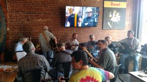 Musicians seated in an oval in the Speakeasy at Tyler's Taproom; one musician holding a guitar is standing up. Participants visible in this picture include guitar players, fiddler players, and banjo players. Background: a brick wall with a large TV hanging in the middle of it (the TV is on), and a Duvel poster hangs to the right of the TV; to the left side of the picture, there is a table with someone's plate of food and a partially consumed drink..
