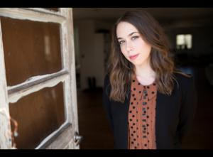 Promotional photo of Sarah Jarosz; she is shown from the waist up, wearing a polka-dotted shirt and black jacket, standing beside a door.