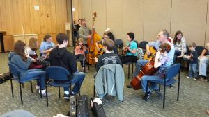 Youth fiddle players, mandolin players, and a cello player sit in a circle to jam; jam facilitators Tatiana Hargreaves on fiddle and Lynda Dawson on guitar were also joined by a bass player and another guitar player, and some family members listen to the jam from seats around the circle.