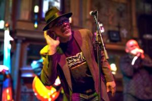 Blues musician Logie Meachum stands at a microphone, right hand up to his right ear; another musicians is partly visible behind him. Meachum wears a hat, dark glasses, a sport jacket, t-shirt, and jeans.
