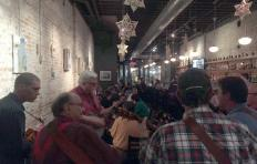 In the foregrounds, backs of musicians gathered in the Busy Bee Cafe during the PineCone Bluegrass Jam
