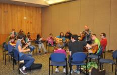 A group of female and male students sit in a circle in a room at Marbles Kids Museum playing fiddles and guitars; facilitator Jef Walter stands to play his guitar in the circle with the students; a few parents and others look on from outside the circle of young musicians.