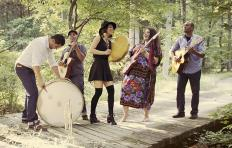 Dark Water Rising promotional photo: 5 people on a wooden platform with trees and grass visible in the background; a man bends over hitting an upright drum, and a trumpet stands on its bell beside the drum; a second man plays guitar; a woman holds a hand drum in her left hand and a drum mallet in her right hand; a second woman holds an electric bass; and a third man holds a guitar.