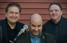 Kruger Brothers promotional photo shows Jens Kruger, Joel Landsberg, and Uwe Kruger standing side by side from the shoulders up, and the neck of Jens' banjo is behind Joel's right shoulder