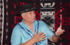 Storyteller Lloyd Arneach wears a wide brimmed hat, a prominent ring on his right ring finger, and a short-sleeve shirt; his hands are up in front of his chest, mid-gesture/story. A patterned tapestry is in the background.