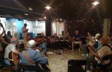 Some musicians gathered in a circle at the PineCone Bluegrass Jam at Imurj in May 2017. Fiddle players, guitar players, a dobro player, mandolin players, and upright bass player share a tune.