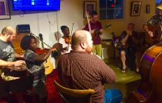 People of various ages and ethnicities gathered in a circle at Imurj during one of the 2017 PineCone Bluegrass Jams.