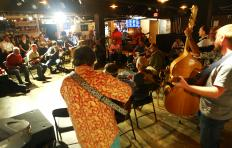 Musicians playing mandolins, fiddle, banjo, guitar, and bass are gathered in a circle at Imurj during the PineCone Bluegrass Jam. Most are seated in folding chairs, a bass player and a couple of guitar players are standing. A few observers are seated on stools with their backs to the bar/counter.