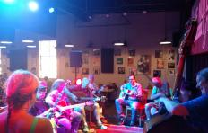Musicians gathered in a circle at The Blue Note Grill; most seated, but three are standing: a man playing bass, a woman playing fiddle, and a man playing guitar. There are multiple guitar players.
