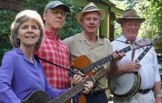 Piney Woods Boys from left to right: Margaret Martin (with guitar), Matt Haney (with fiddle), Wayne Martin (with guitar), and Jim Collier (with banjo). Trees and part of a building are visible in the background.