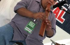 Cherokee storyteller and musician Matthew Tooni playing a wooden flute on stage at the 2017 National Folk Festival. He wears glasses, jeans and a plaid button-down shirt.