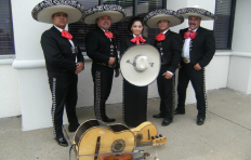 Five people (four men and one woman) stand outside a building in full, matching mariachi outfits: black pants, coats, and shoes, white shirts, red neckerchiefs, and black and silver sombreros (the woman, standing in the middle, holds her sombrero in front of her). On the ground in front of the musicians are instruments: a violin, a trumpet, a guitar, and another string instrument that looks like a small guitar.