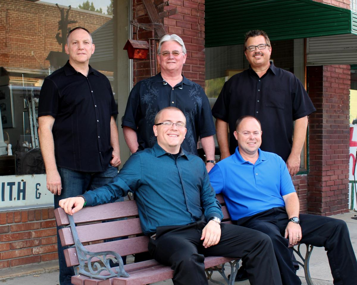 Members of The Grass Cats - 3 standing side by side behind a bench, 2 sitting on the wooden bench, outdoors in front of a  brick building. All 5 men wear dark pants and button down shirts in various shades of blue.